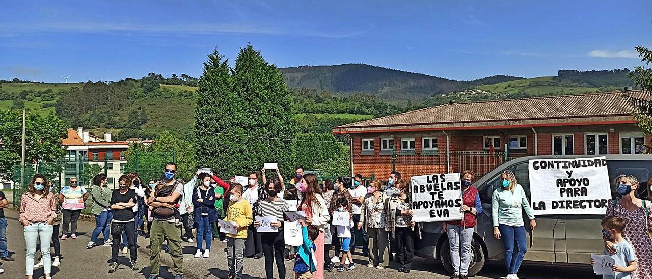 Las familias que apoyan a la actual dirección del colegio de Candamo, ayer, delante del centro. A la derecha, el grupo de padres y madres que exigen una investigación en el colegio candamín.   S. A.