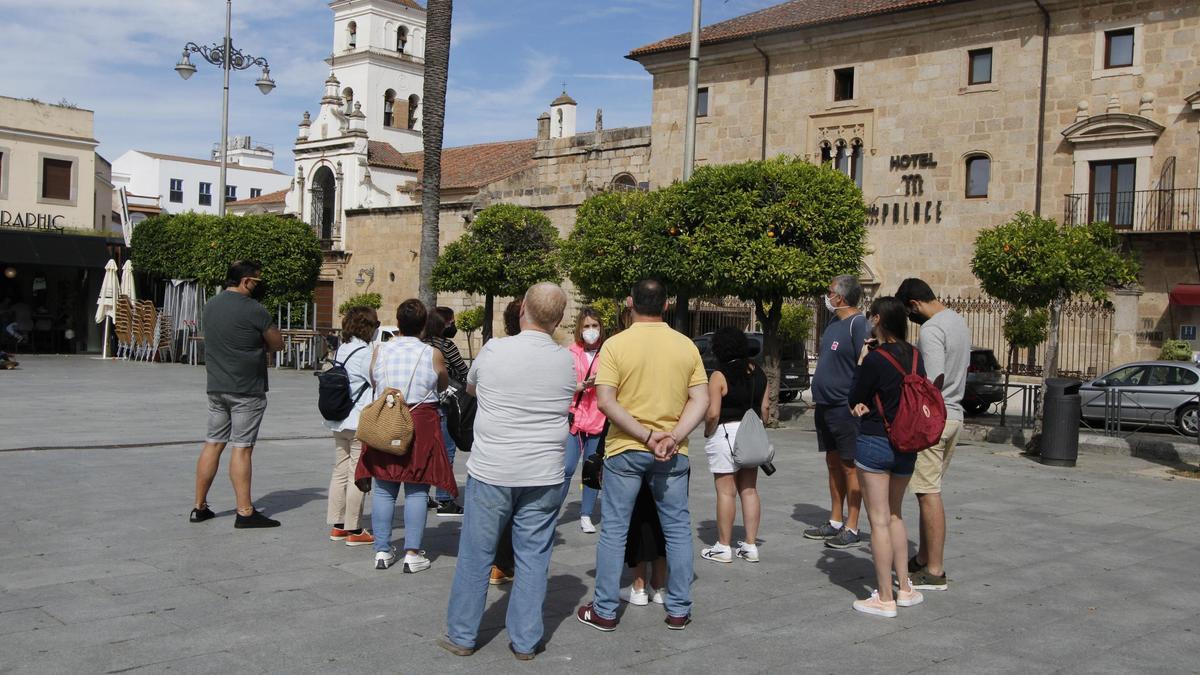 Turistas en una visita guiada en la plaza de España de Mérida.