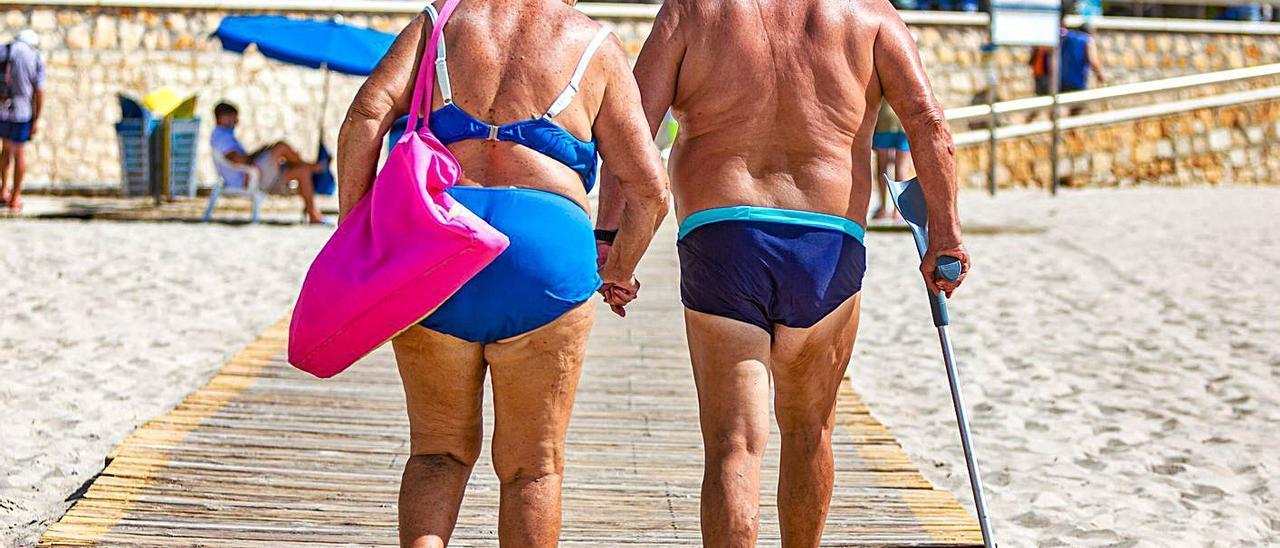 Dos turistas mayores salen por una de las pasarelas tras una jornada playera en Benidorm.