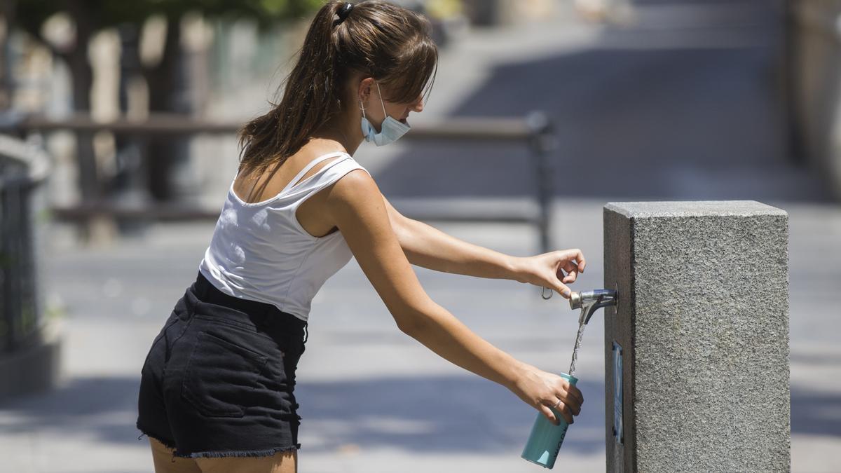 Una mujer llena una botella de agua de una fuente en foto de archivo.