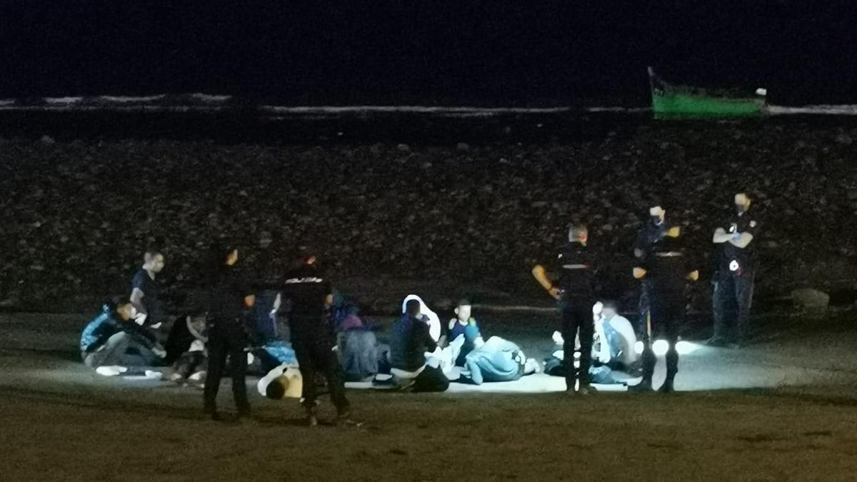 Inmigrantes frente al Faro de Maspalomas. Al fondo, la patera en la que llegaron.