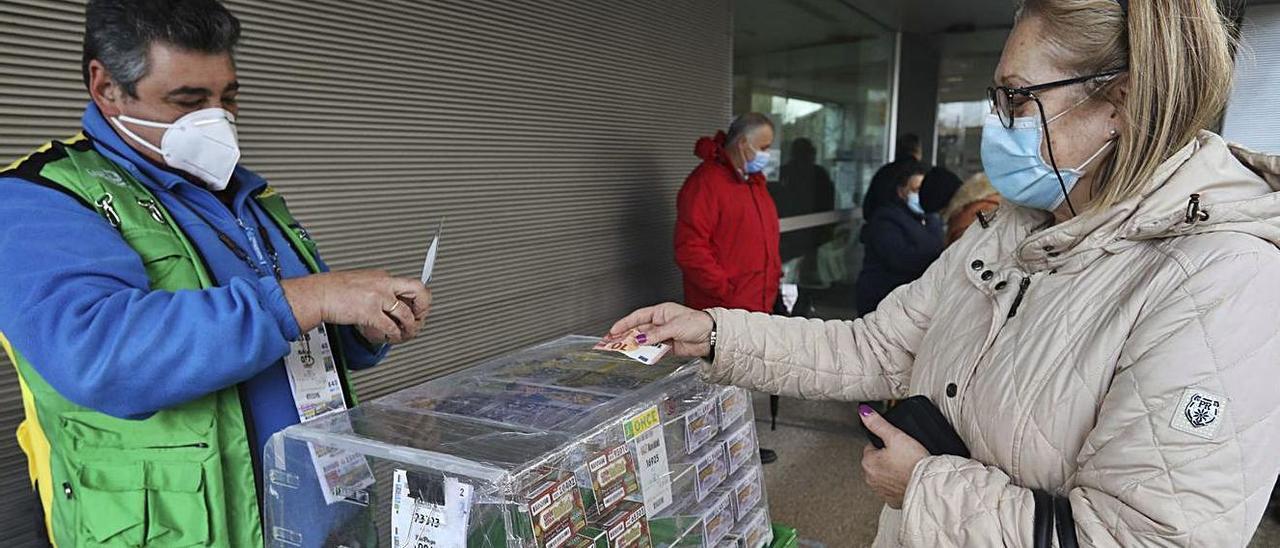 Óscar Moro vende unos cupones en la puerta del centro de salud de La Luz, ayer, a mediodía.   Ricardo Solís