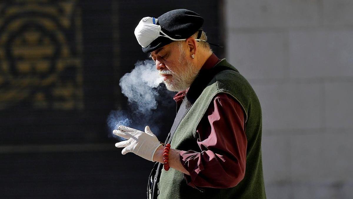 Un hombre fuma en la calle en Valencia.