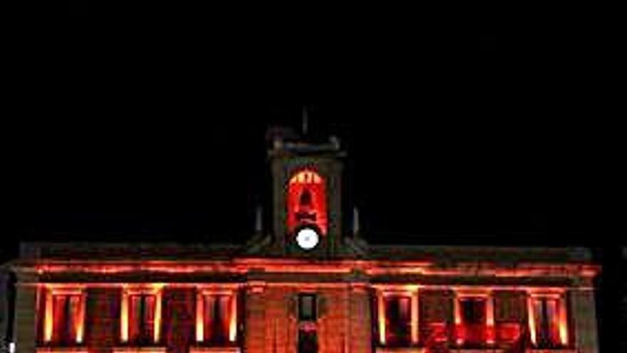 Fachada de la Casa de las Panaderas iluminada de rojo.