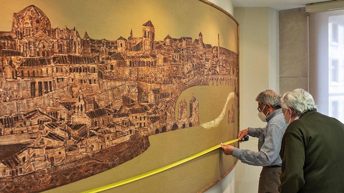 """Antonio Pedrero observa al restaurador mientras mide la obra """"Zamora"""" en la sala de juntas de la oficina del BBVA en la plaza de la Constitución."""