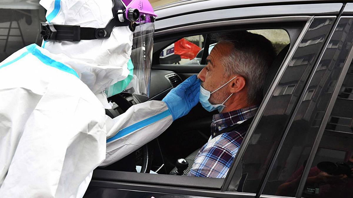 Un hombre se somete a una PCR en el 'Covidauto' de O Ventorrillo. |   // VÍCTOR ECHAVE