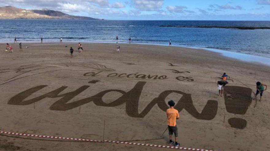 Una enorme postal de arena  en la playa de Las Canteras reivindica la vida en el Día Mundial de los Océanos
