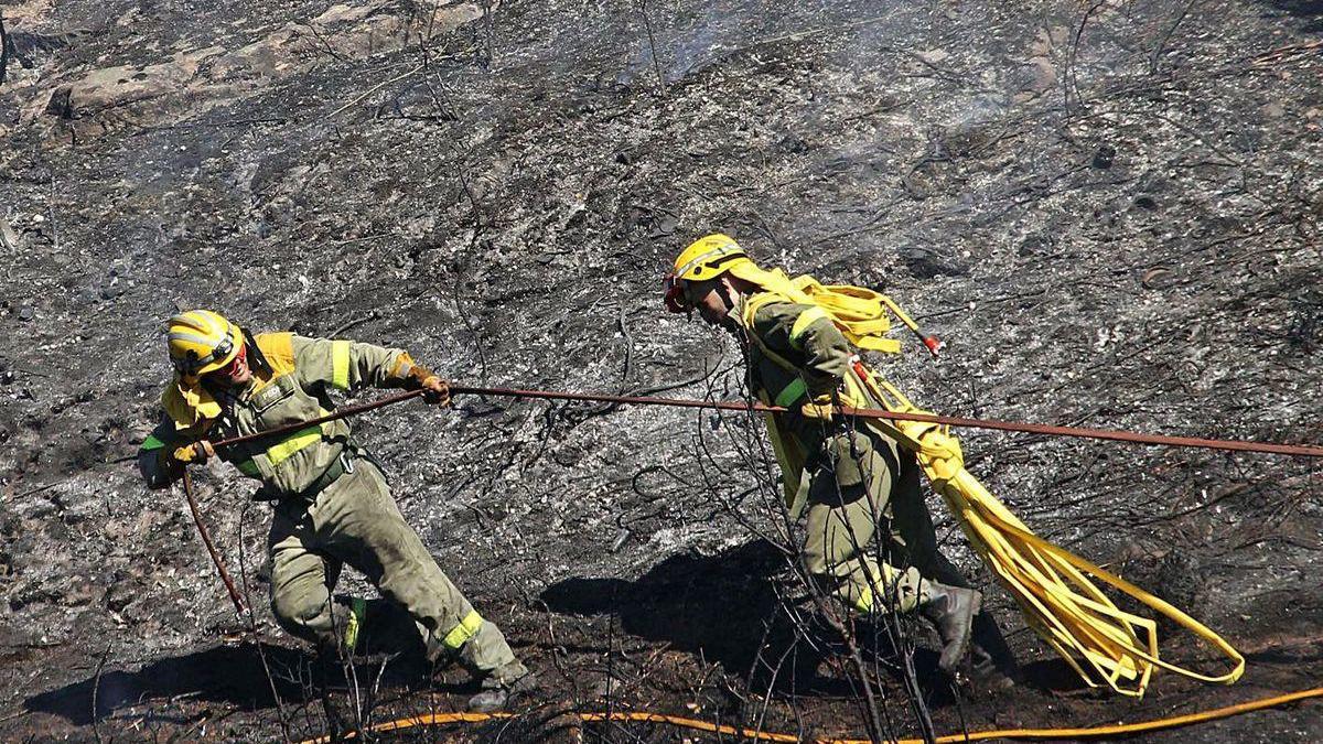 Operarios de la brigada antiincendios trabajan sofocando un fuego.