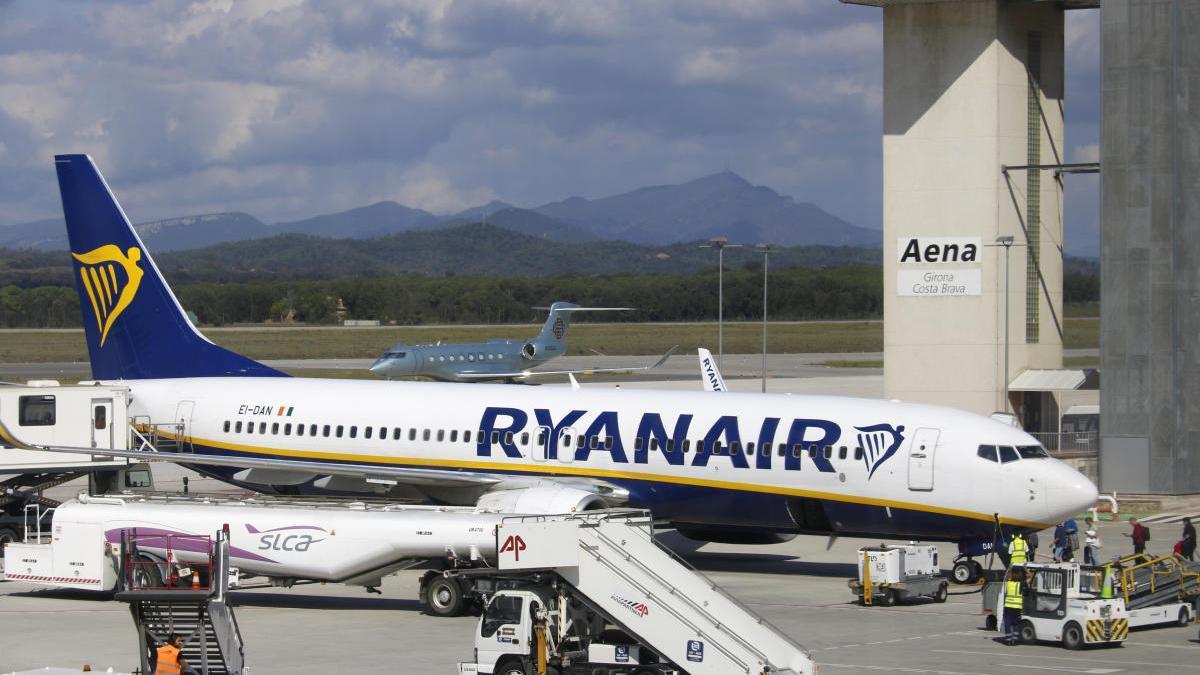 Pla obert d'un dels avions de Ryanair aterrats a l'Aeroport Girona-Costa Brava amb la torre de control de fons.