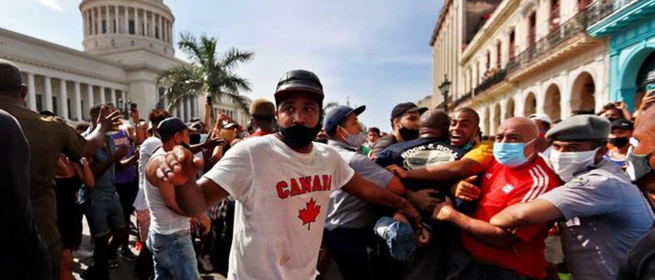 Policías arrestan a manifestantes frente al capitolio de Cuba, en La Habana.