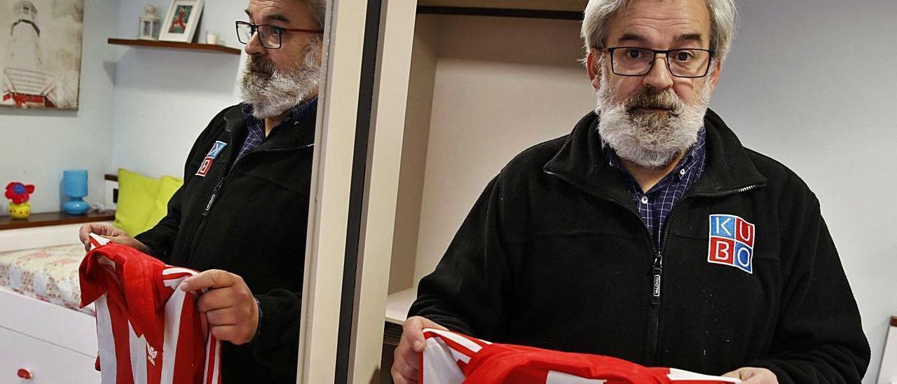 Roberto Entrialgo, con una camiseta del Sporting de su época, en su lugar de trabajo. | Ángel González