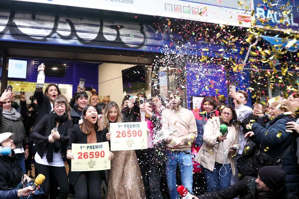 Agraciados por el Premio Gordo del Sorteo Extraordinario de Lotería de Navidad 2019 posan con el número premiado, el  26590, en la famosa administración de 'Doña Manolita'.