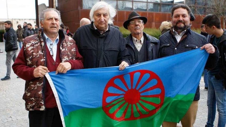 Cuatro hombres sostienen la bandera del pueblo gitano.