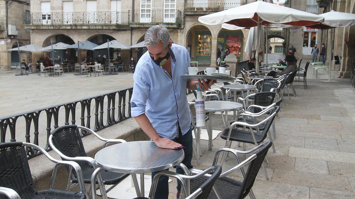 Un camarero en la terraza de una cafetería de Ourense antes del último cierre de la hostelería en Galicia. // Iñaki Abella