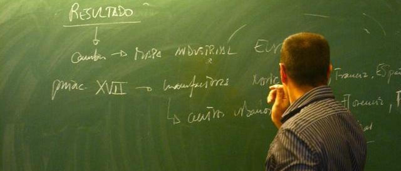 Un profesor universitario escribe en una pizarra mientras imparte una clase