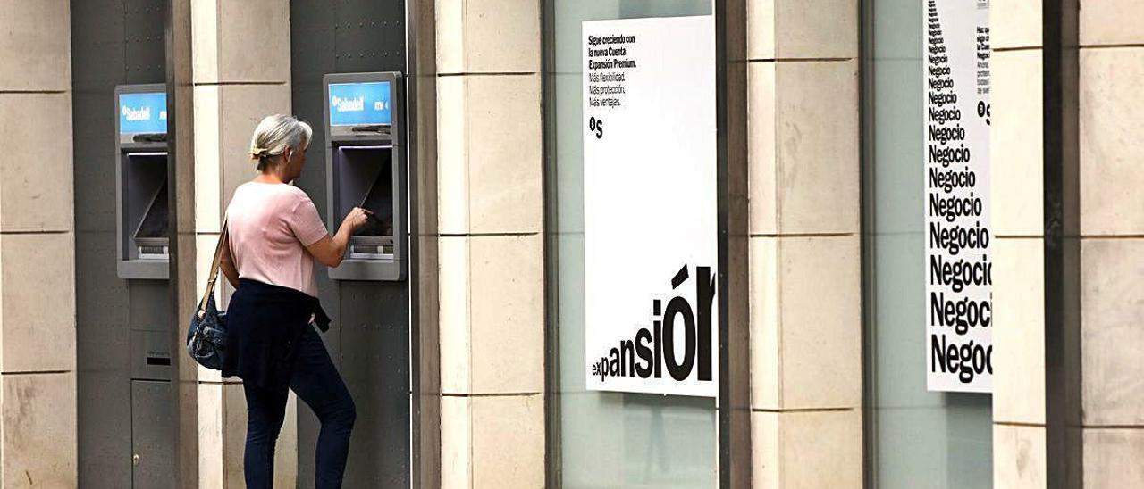 Una mujer saca dinero de un cajero de València, en una imagen de archivo.