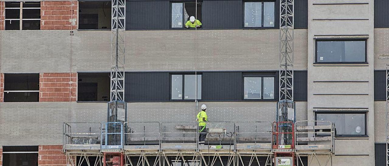 Operarios de la construcción trabajan en una promoción de pisos en Alicante.