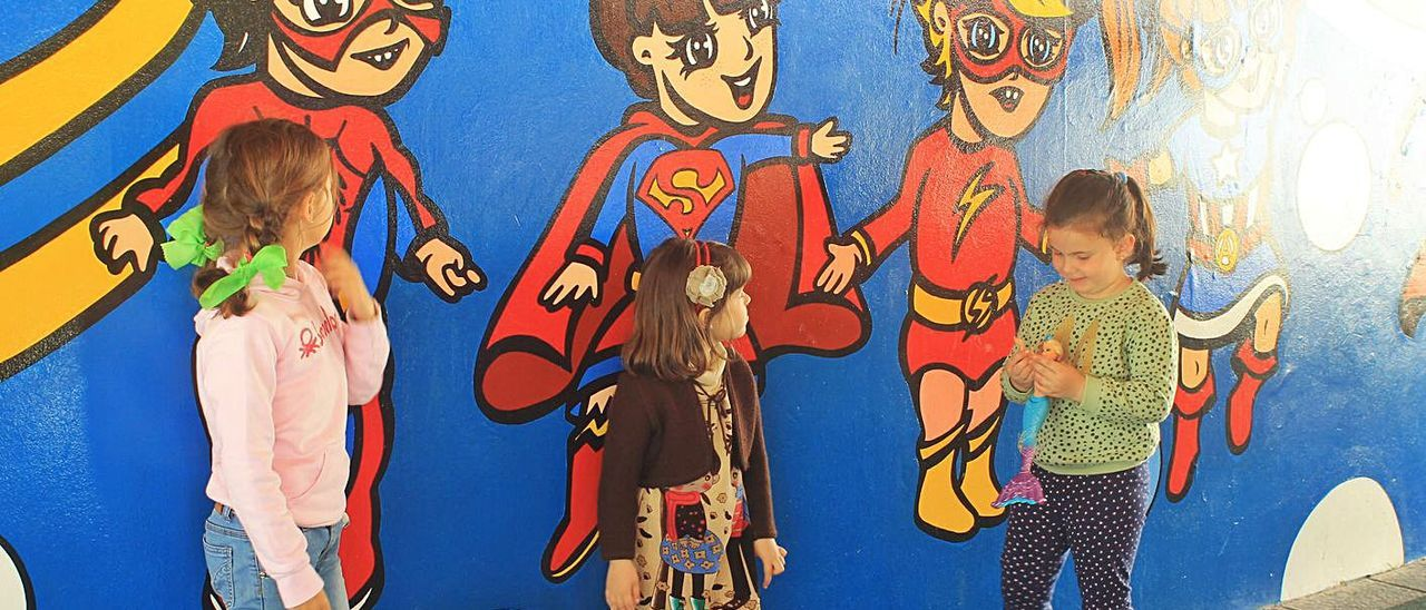 Tres niñas junto al mural del parque de Les Conserveres de Candás, cuando fue inaugurado en 2015.   LNE