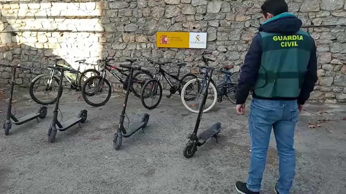 Un guardia civil, con los patinetes y bicicletas recuperados.