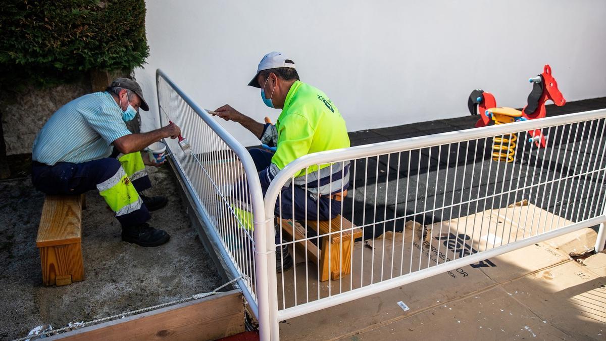 Dos operarios repintan una valla en A Coruña.