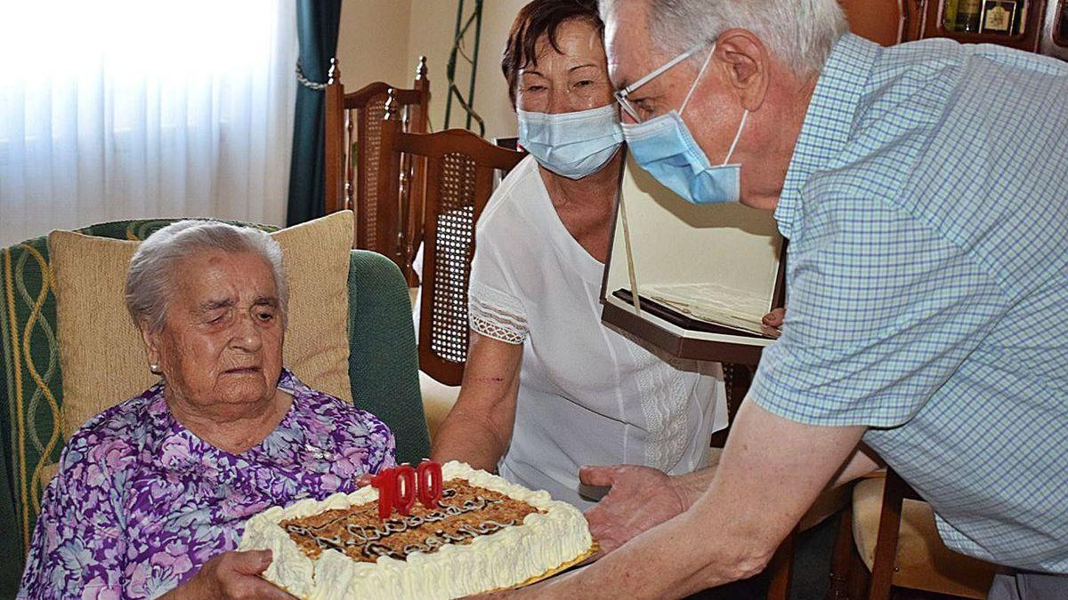 El alcalde de Valga entrega la tarta de cumpleaños a la nueva centenaria, Regina Grela.
