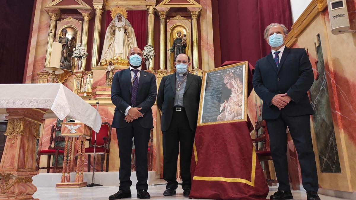 El hermano mayor de la Merced, el párroco de San Antonio y el concejal Salvador Fuentes, junto al cartel.
