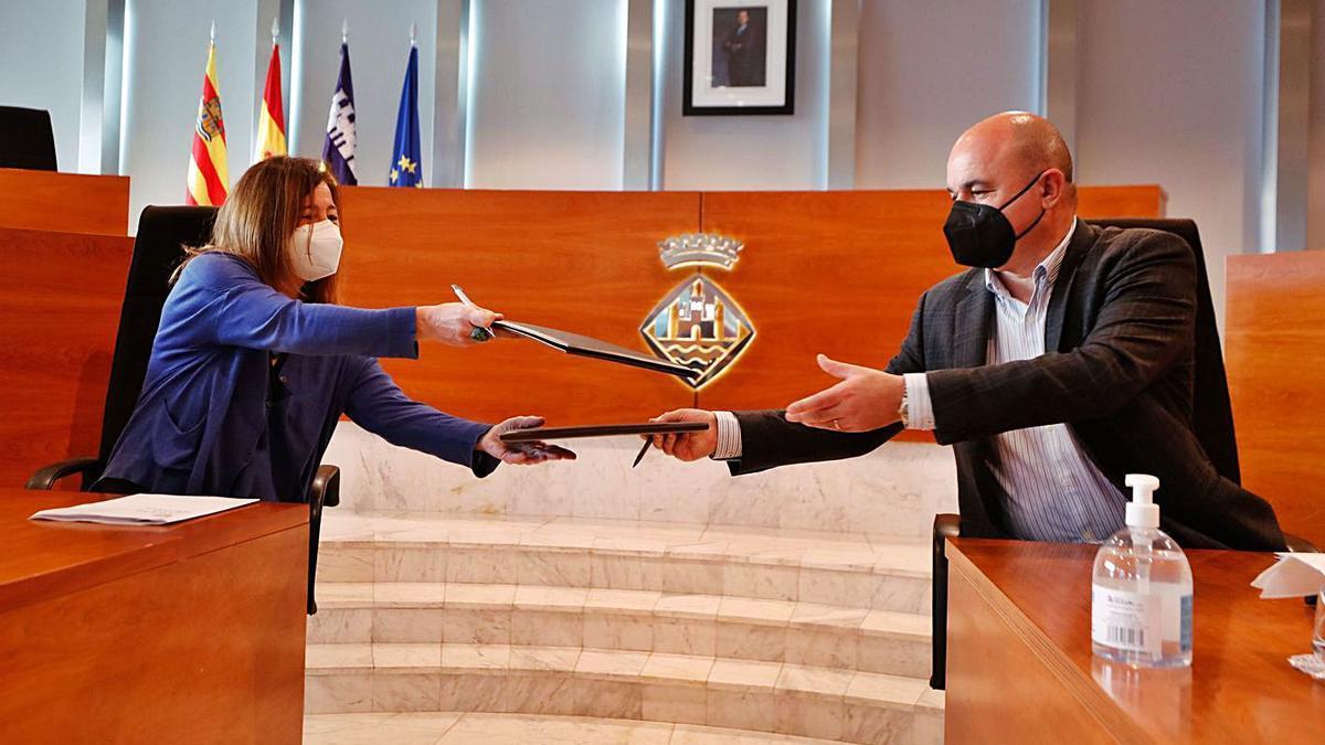 Armengol y Marí se intercambian las carpetas durante la firma del convenio. | J. A. RIERA