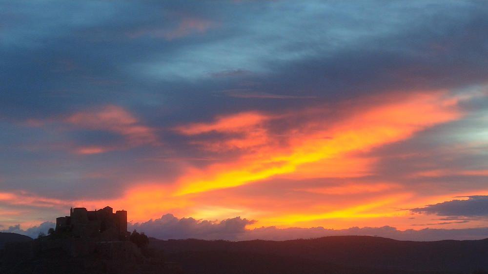 Cardona.  La baixada de temperatura de la setmana passada ens va regalar una bonica albada, amb un cel rogent espectacular i uns núvols densos que, amb la figura del castell de Cardona, fan d'una sortida de sol una obra d'art.
