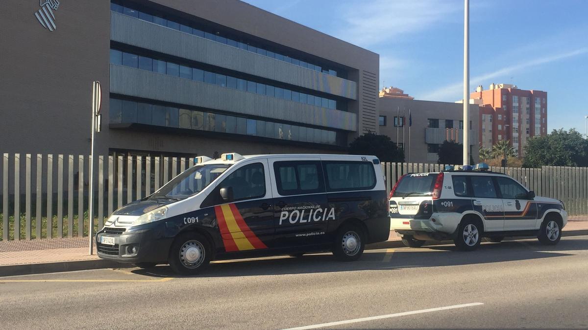 Un furgón y una patrulla de la Policía Nacional, frente a la Ciudad de la Justicia.