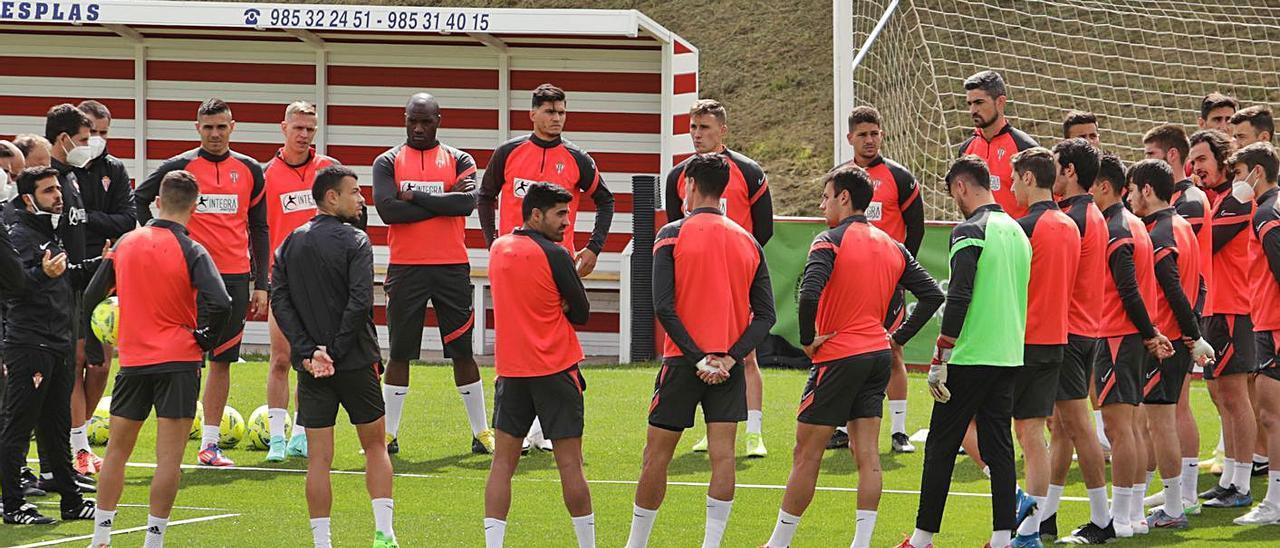 Cuerpo técnico y jugadores formando un círculo sobre el césped antes de comenzar a entrenar. | Juan Plaza