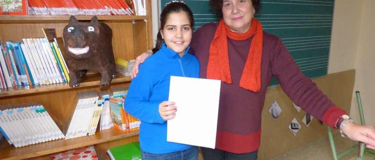 Ainara Mayo, con su cuento en la mano, junto a su profesora Carmen Guardado.