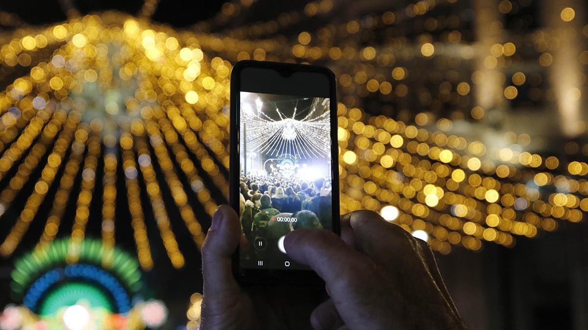 Una persona graba las luces del año pasado con su teléfono móvil // Alba Villar