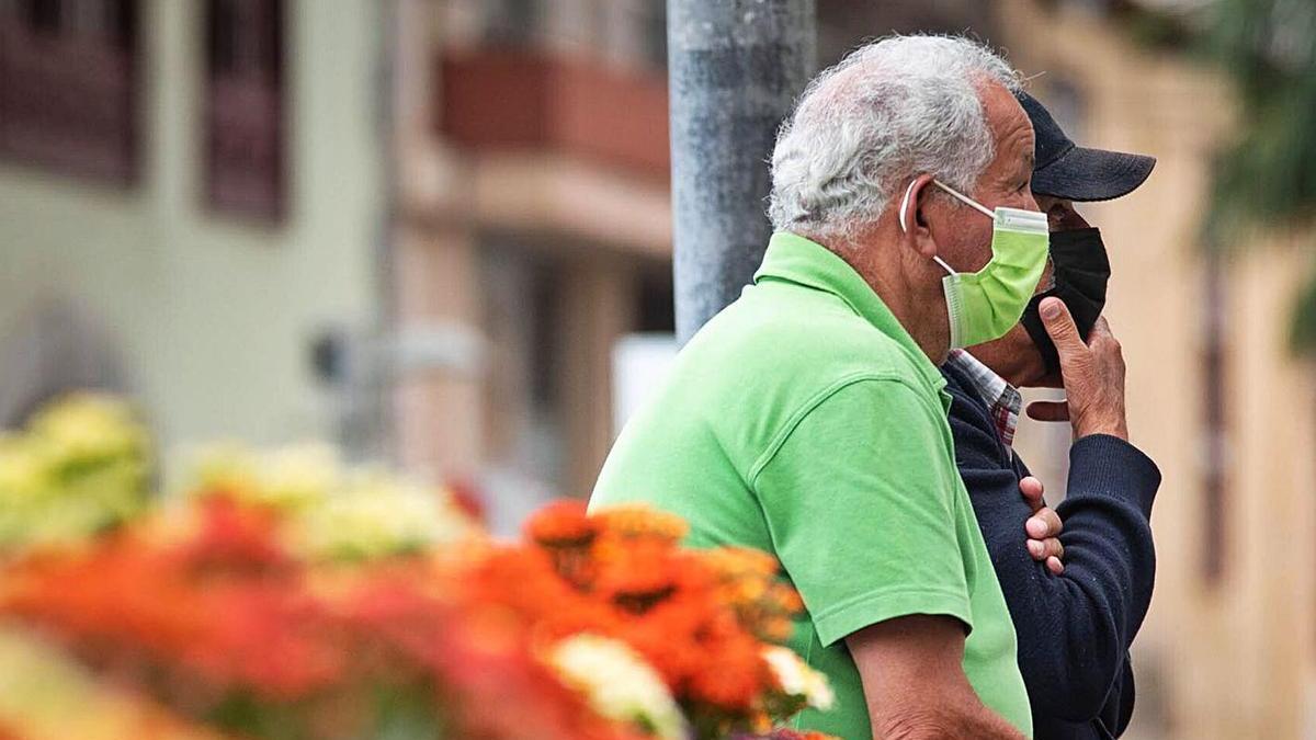 Dos hombres conversan en una plaza de Puerto de la Cruz.