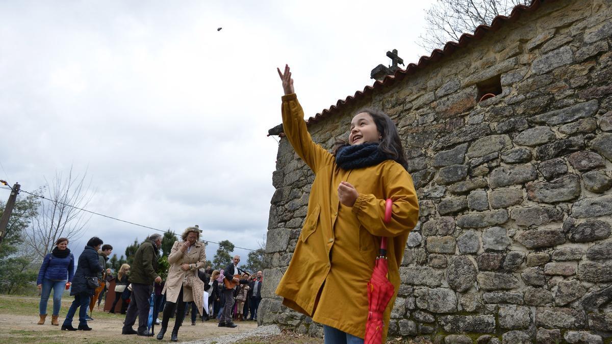 Una niña lanza una piedra a la cubierta de la ermita de Sin Cibrán.