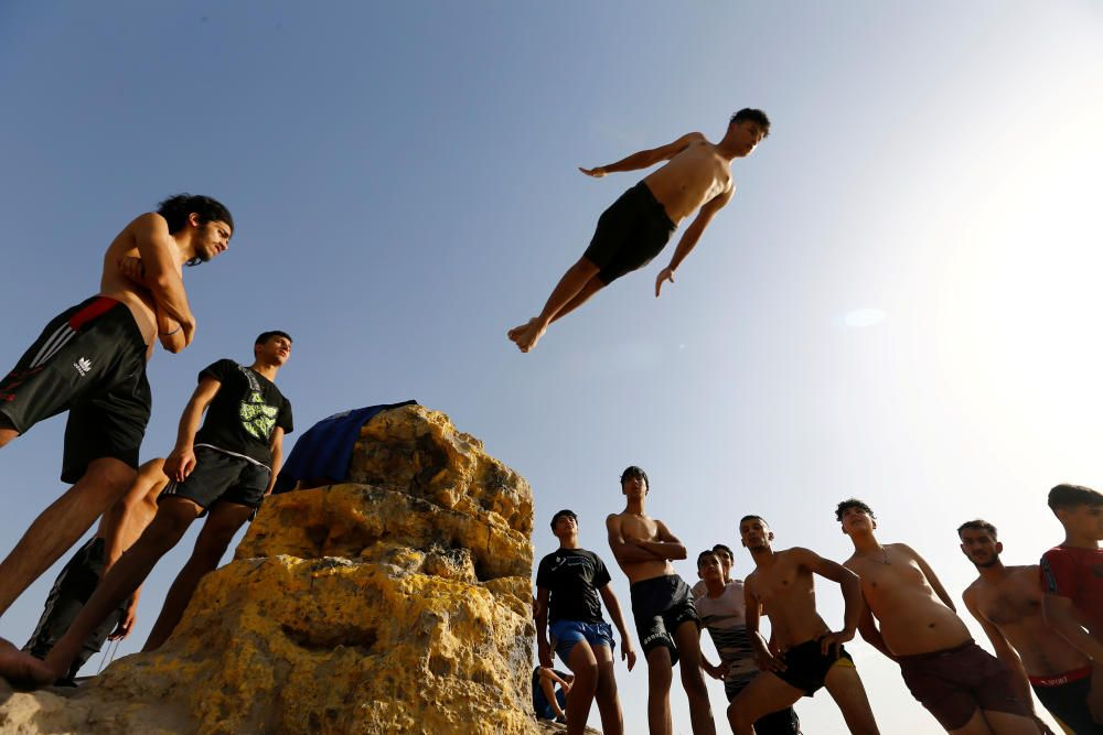 A boy dives into the Tigris river to cool down, ...