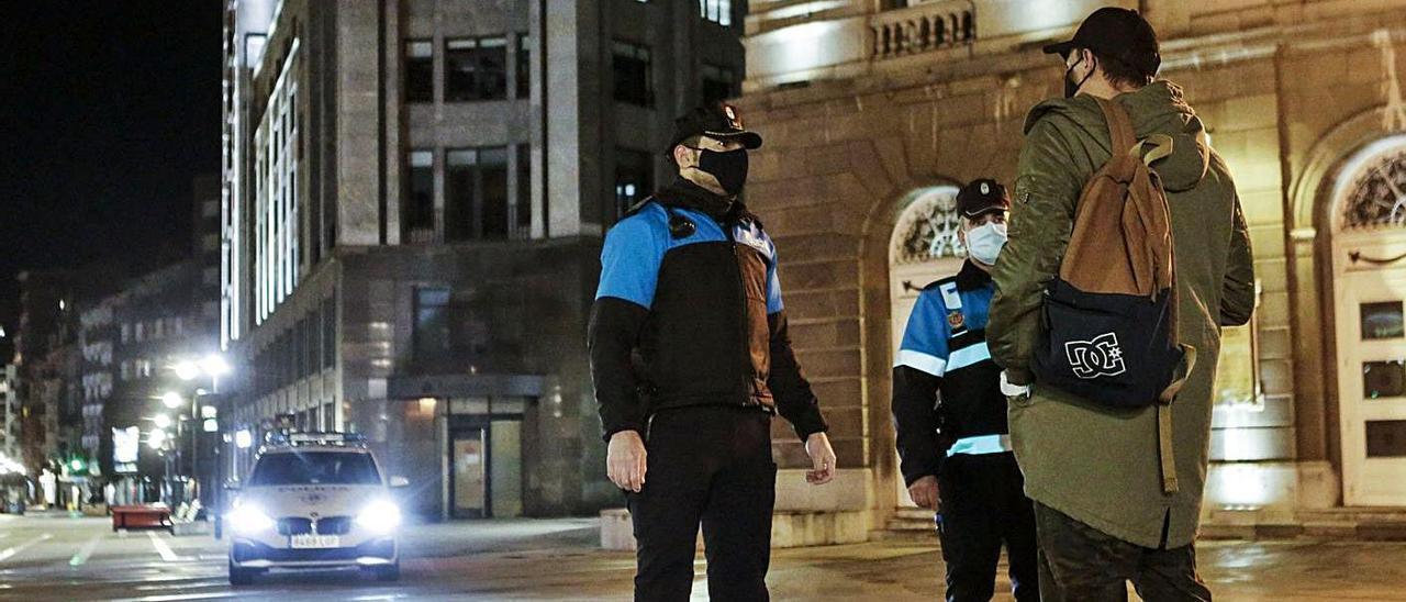 Dos agentes de la Policía Local realizando un control, ayer en Oviedo, ante el teatro Campoamor, minutos después de que comenzara el toque de queda. | Julián Rus