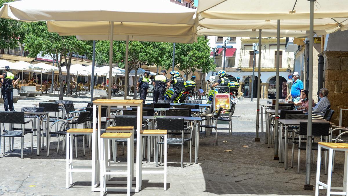 Mesas vacías en la plaza Mayor, con policías al fondo.