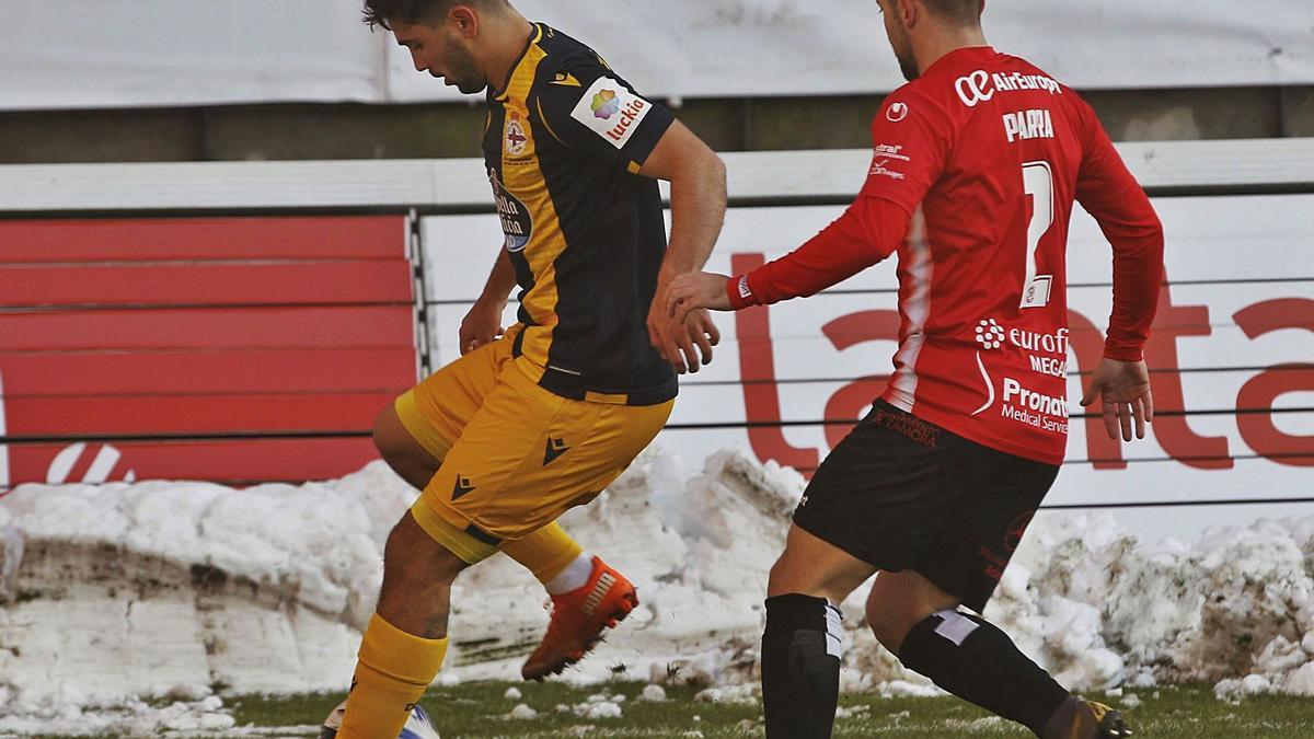 El deportivista Rui Costa protege el balón ante Parra.    // LOF