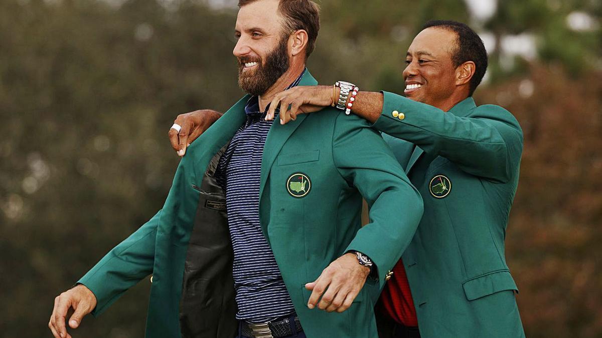 Tiger Woods, ganador el año pasado, coloca la chaqueta verde a Dustin Johnson. |  // EFE