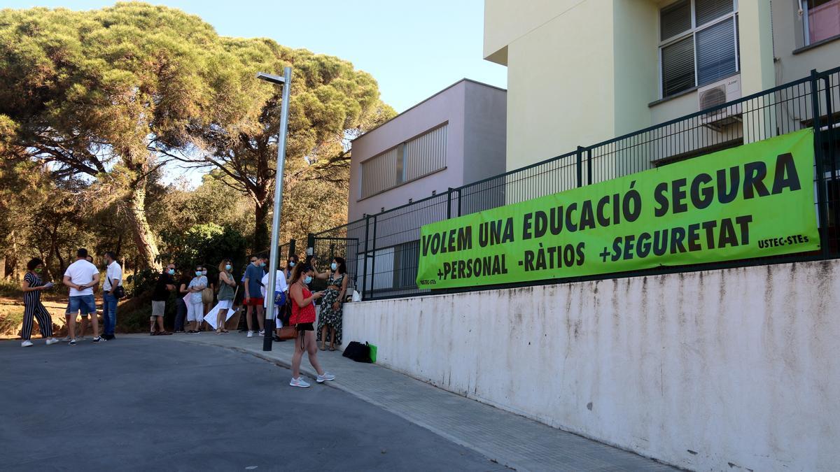 En primer terme, la façana de l'escola d'educació especial Els Àngels de Palamós; al fons, la protesta aquest 21 de juny del 2021 (Horitzontal)