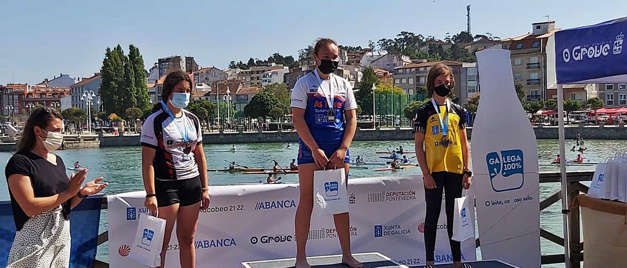 La palista Tania Álvarez (izquierda) entregó las medallas al podio de la categoría C-1 infantil B. |  // FDV