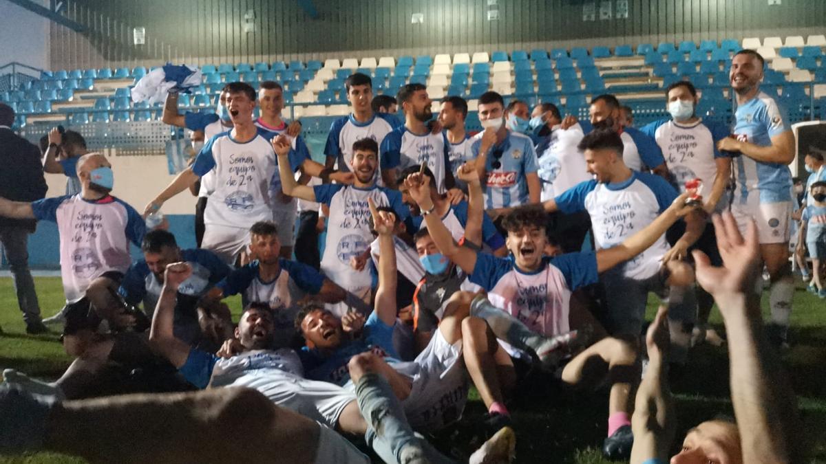 Los jugadores del Coria, eufóricos sobre el césped de La isla tras conseguir el ascenso a Segunda RFEF.