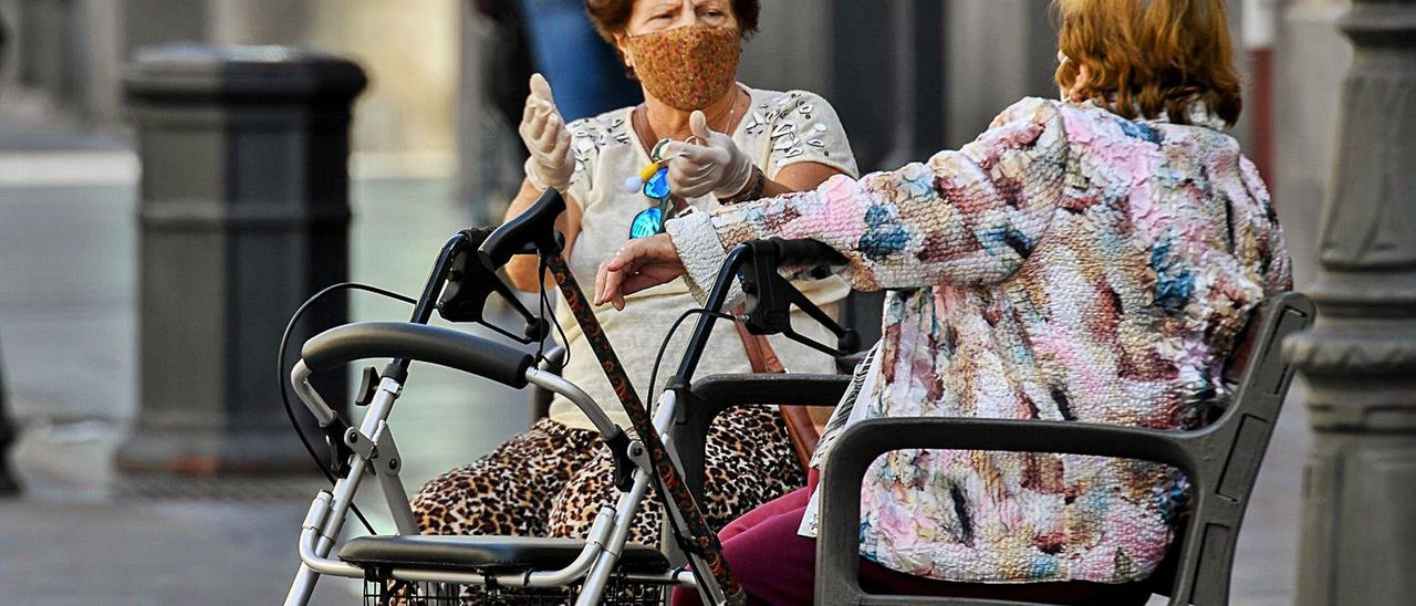 Dos señoras charlan sentadas en un banco. | | JUAN CASTRO
