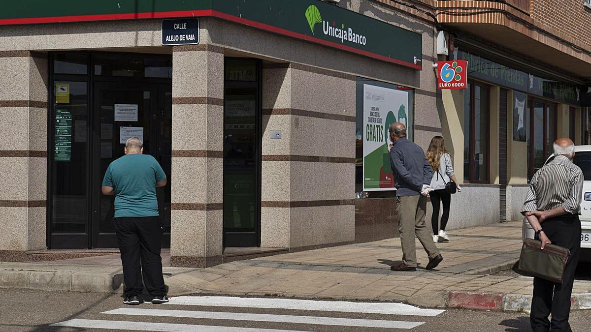 Varias personas esperan en el exterior de una oficina bancaria en Morales del Vino.   José Luis Fernández