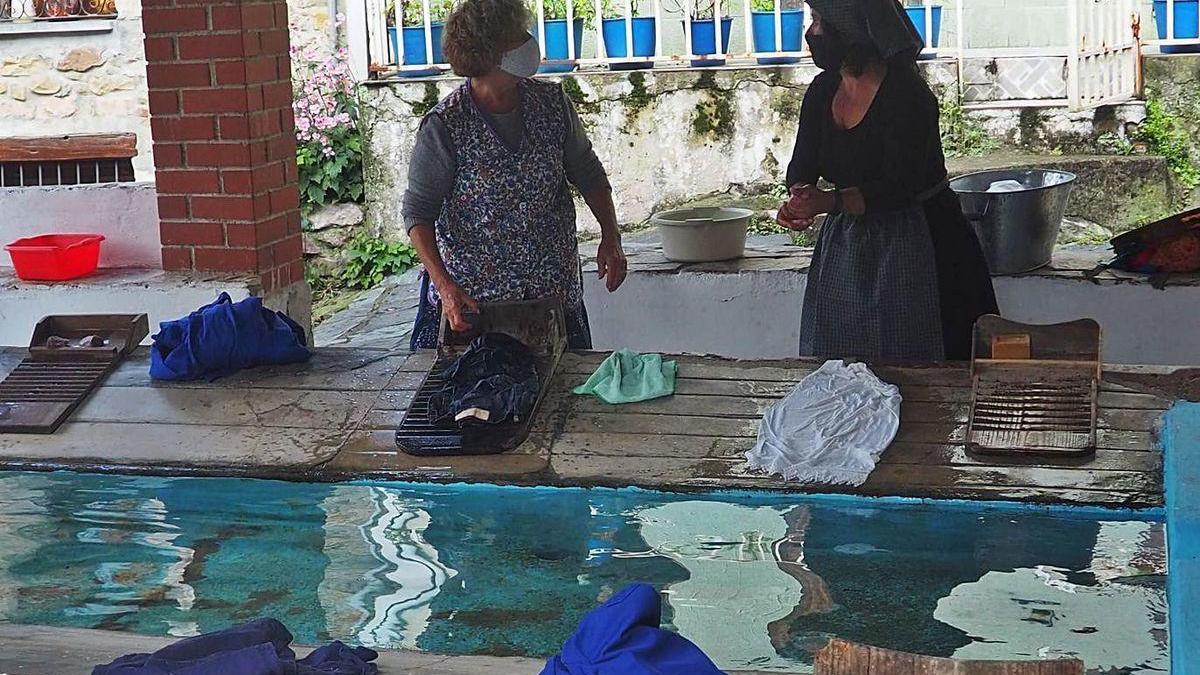 Dos vecinas hacen la colada en el antiguo lavadero durante la ruta guiada.