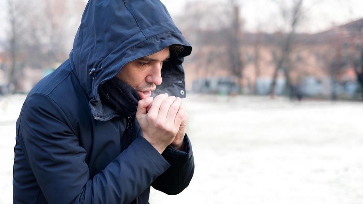Un hombre calienta sus manos