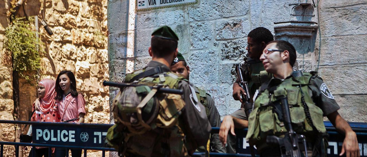 Dos jóvenes palestinas pasan ante una  patrulla israelí en el barrio  musulmán de  la ciudad antigua  de Jerusalén. GERMÁN CABALLERO