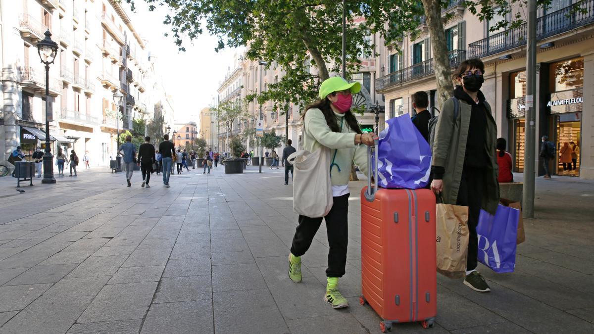 Dos turistas pasean con sus maletas por una calle.