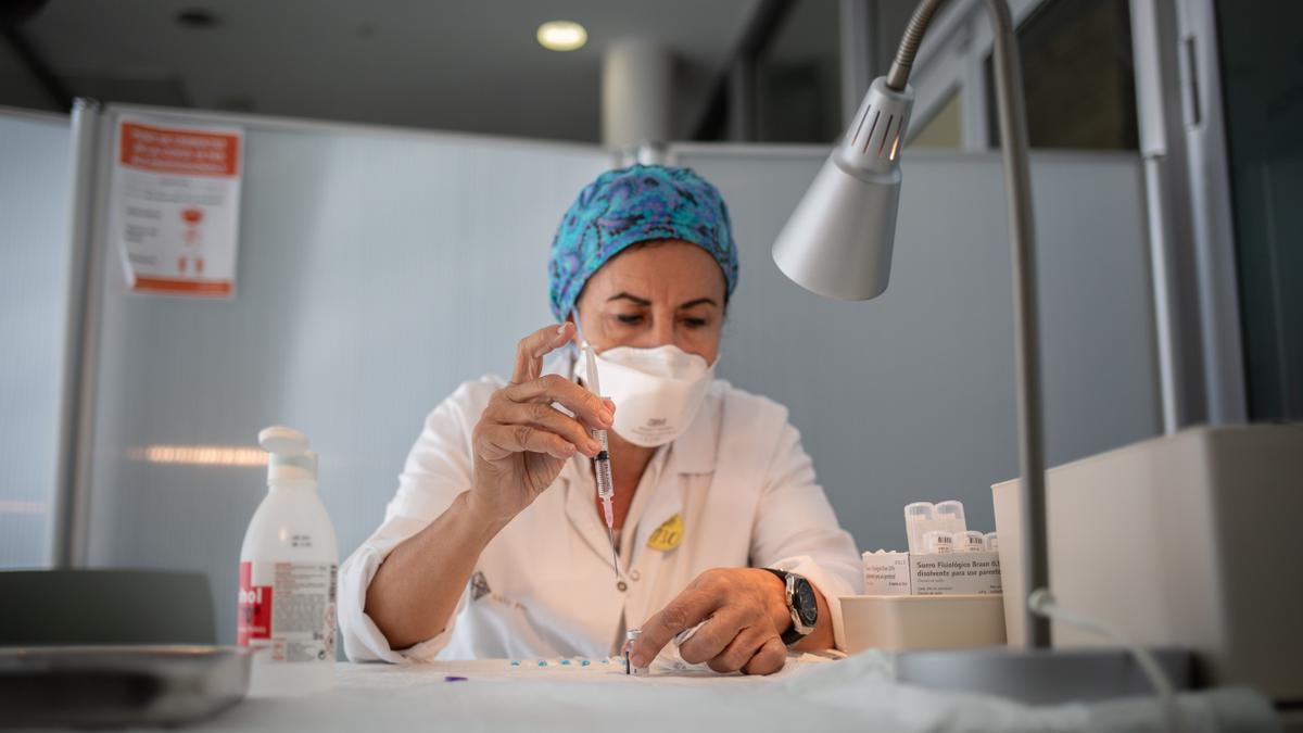 Una enfermera prepara una vacuna contra el COVID.