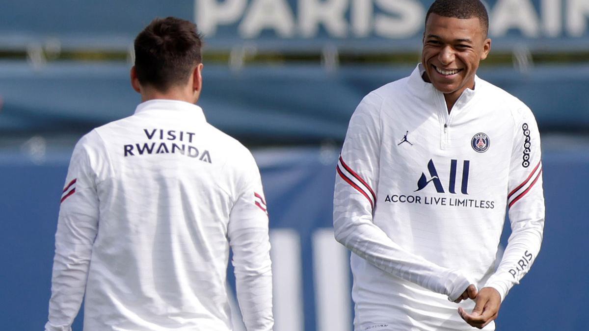 Mbappé sonríe ante Messi, de espaldas.